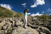 woman on ocean of rocks