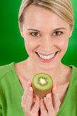 Healthy lifestyle - happy woman holding kiwi