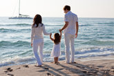 happy young family with little daughter on the beach at wasse