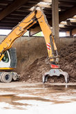 excavators with gripper arm in front of a large pile of brown earth