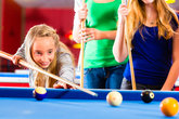 girl playing snooker with family