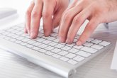 Close-up Of Male Hands Typing On Computer Keyboard