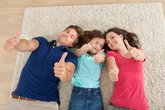Confident Family Gesturing Thumbs Up At Home