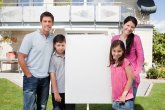 Small family standing outside with a empty sign