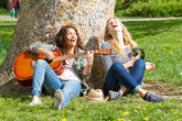 two girlfriends making music in the park