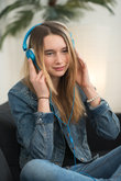 teenager sitting at home on the sofa and listening to music on headphones