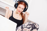 young woman listens to music on the computer with long red hair