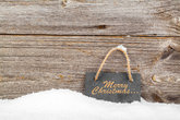 Black board of slate on old wooden background,with snow