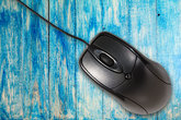 Computer mouse on the blue wooden  background