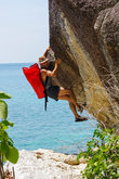 strong and happy man climbing on high rock over the sea with a hut   red seabag.