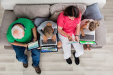 Family With Their Laptop And Digital Tablet At Home
