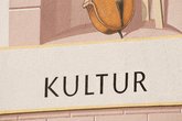 the word culture and part of a musical instrument on a house wall