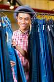 Asian man browsing jeans in fashion store