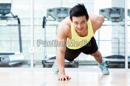 muscular young man doing one armed pushups in gym stock photos