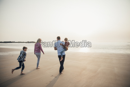 family walking at the beach stock photos