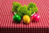 Easter eggs and fresh green salad on red white checkered tablecloth. Health concept.
