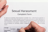 Human Hand Filling Sexual Harassment Complaint Form
