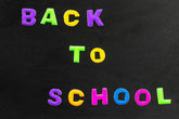 Back to school text written with colorful letters on blackboard. School board isolated on white background. Concept education.