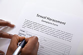 Human Hand Filling Sexual Harassment Complaint Form With Pen