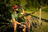 Young man biking on a mountain bike enjoying healthy active lifestyle outdoors in summer (shallow DOF)