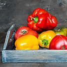 Imperfect natural peppers and tomatoes on an old wooden tray on a dark background. Healthy eating concept.