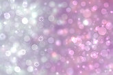 A festive abstract gradient pink gray silver background texture with glitter defocused sparkle bokeh circles and stars. Card concept for Happy New Year, party invitation, valentine or other holidays.